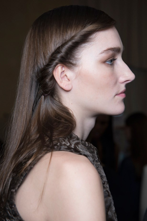 A side-twist updates the usual 'out and glossy' look at Hermes' show. The pinned twist is an ideal place to nestle flowers or bejewelled slides.