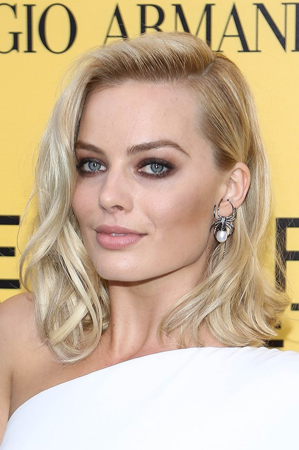 Margot Robbie toughens up her look with a statement spider earring.