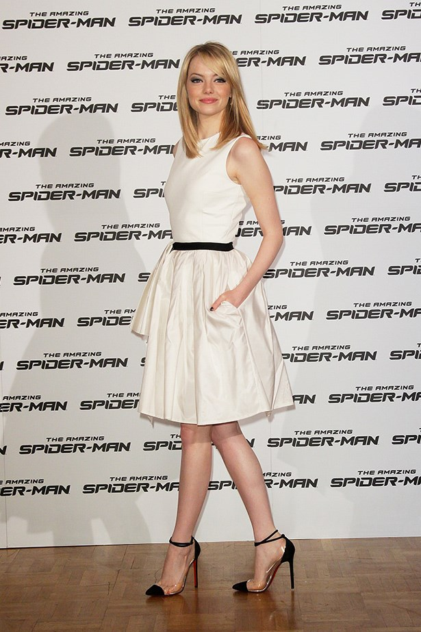 Emma Stone in a chic white dress and Christian Louboutin heels.