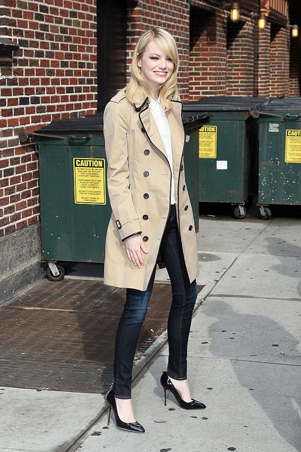 Emma Stone wearing a Burberry trench and blue skinny jeans.