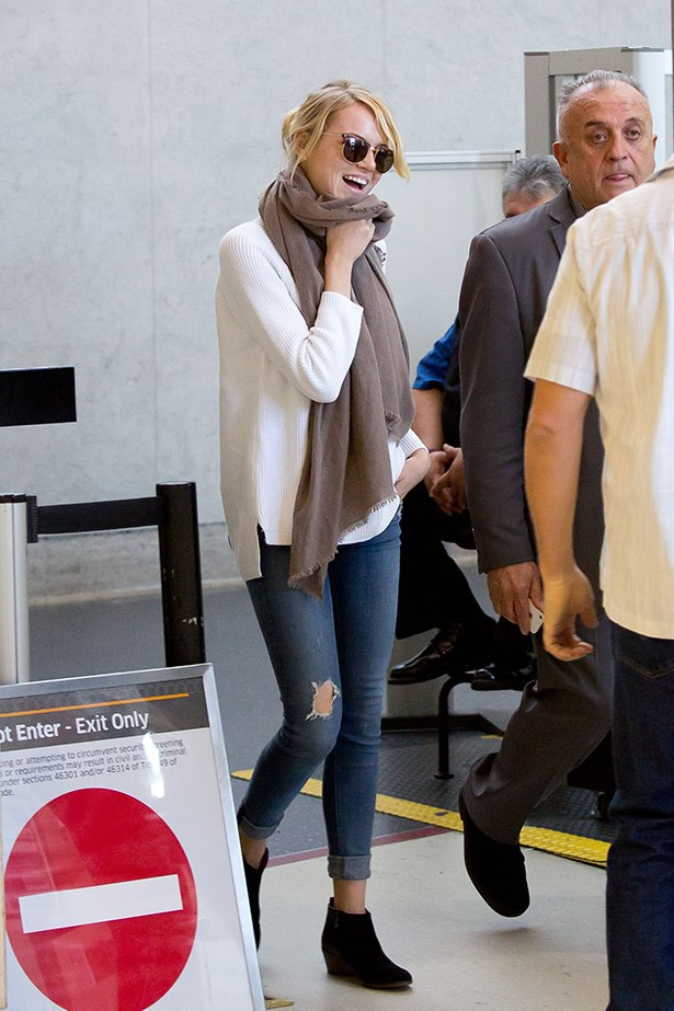 Emma Stone looks chic at LAX in ripped jeans and chelsea boots.
