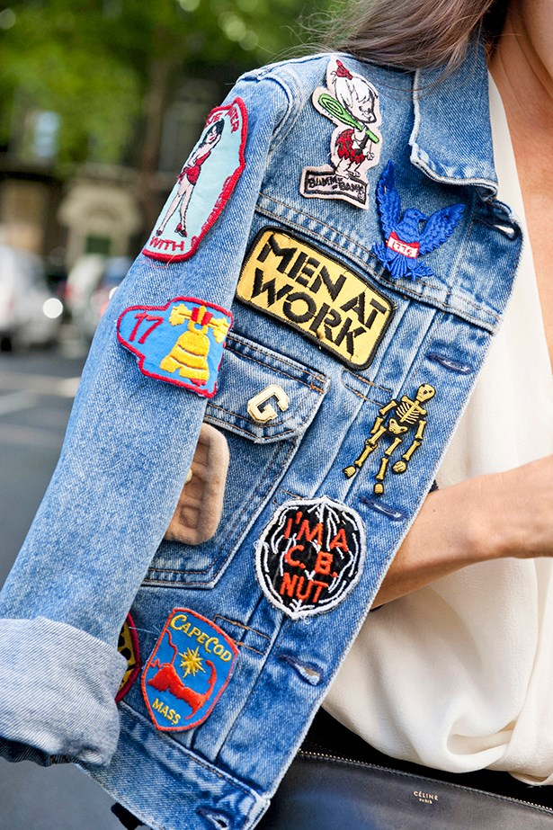 "<p>""Thrown over the shoulders, a denim jacket covered in vintage iron-on patches takes a minimal ensemble to somewhere quite effortless."" </p>"