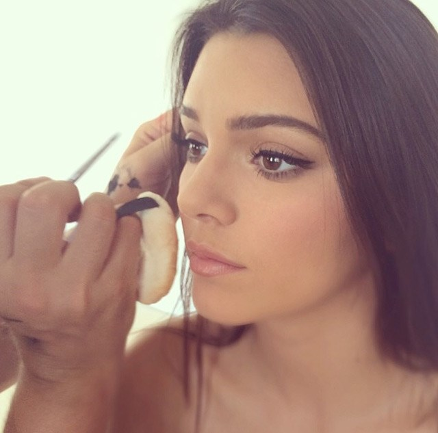 A close up shot of Kendall Jenner's makeup artist putting the final touches on her look.