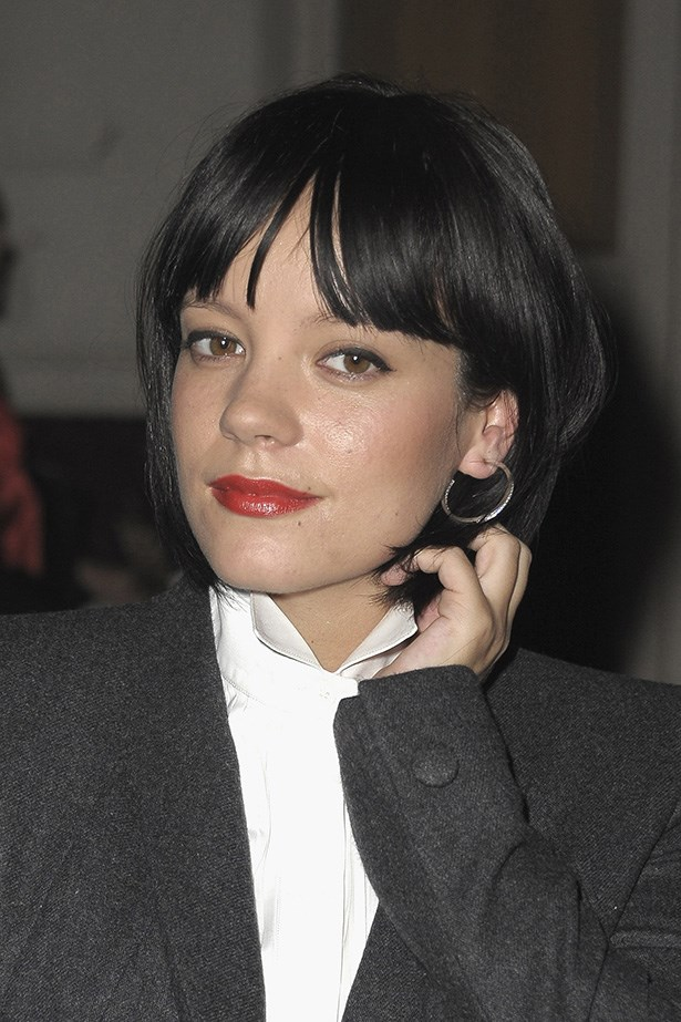 Allen contrasted her sharp men's style suit with a feminine bold red lip and matching blush during Paris Fashion Week in 2010.