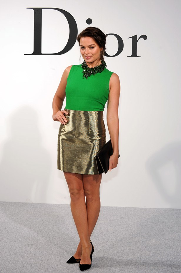 <em>ELLE</em> covergirl Margot Robbie shines in a green silk top, gold  skirt, statement necklace and accessories, all by Dior.