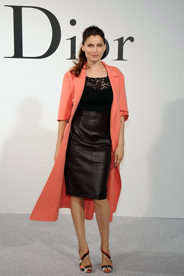 Model Laetitia Casta layered a sweet sherbet cashmere coat over a chic lace top and leather skirt, all Dior.