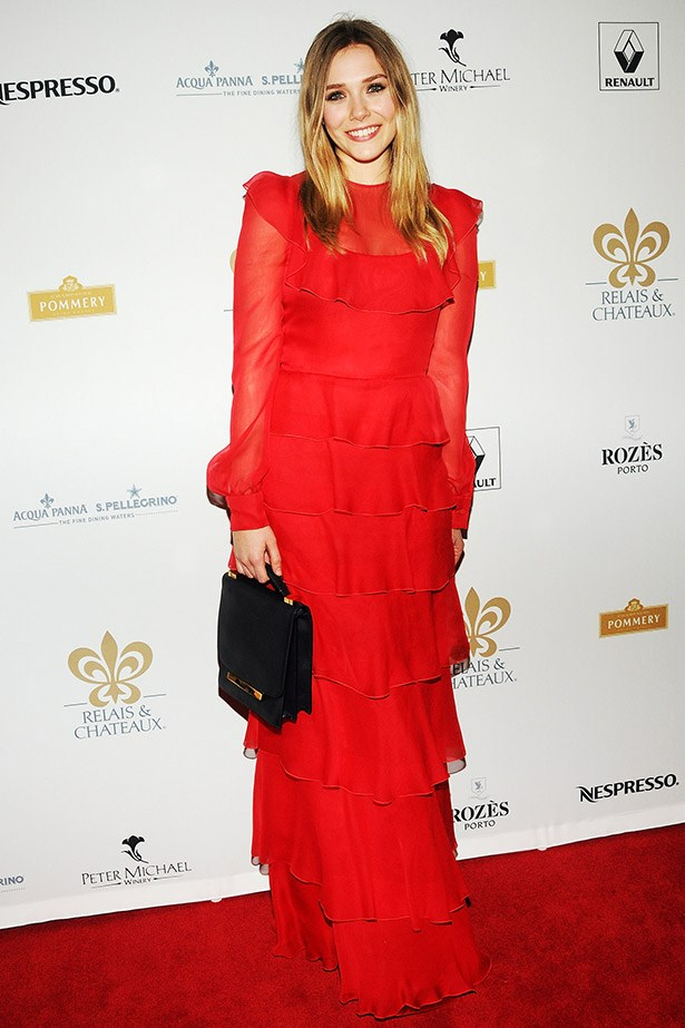 A bold choice for the actress, Olsen chose to wear a fire engine red tiered Valentino gown, paired with a bag by her sisters' label, The Row.