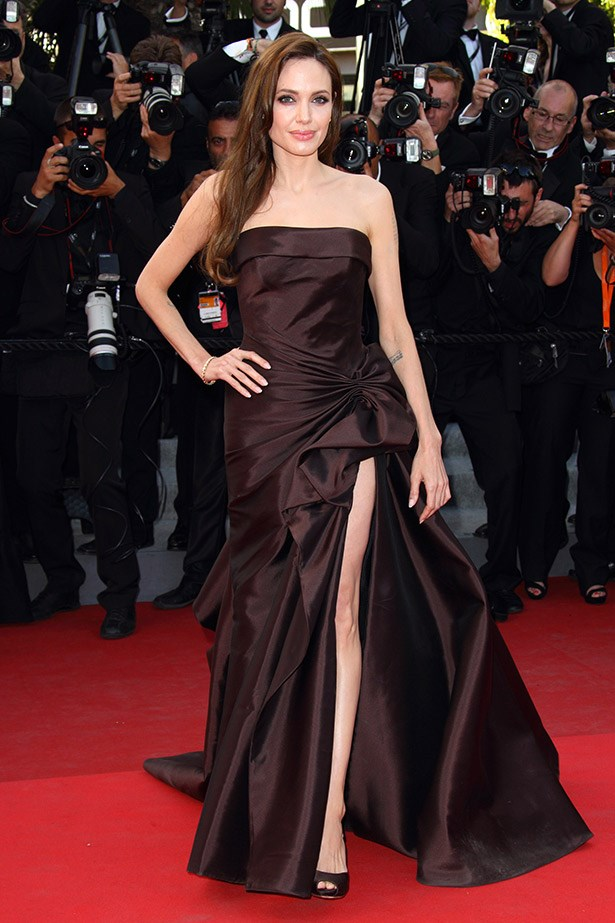 Angelina Jolie shows of her infamous pins in this black strapless dress in  2011 at the premiere of <em>The Tree of LIfe</em>