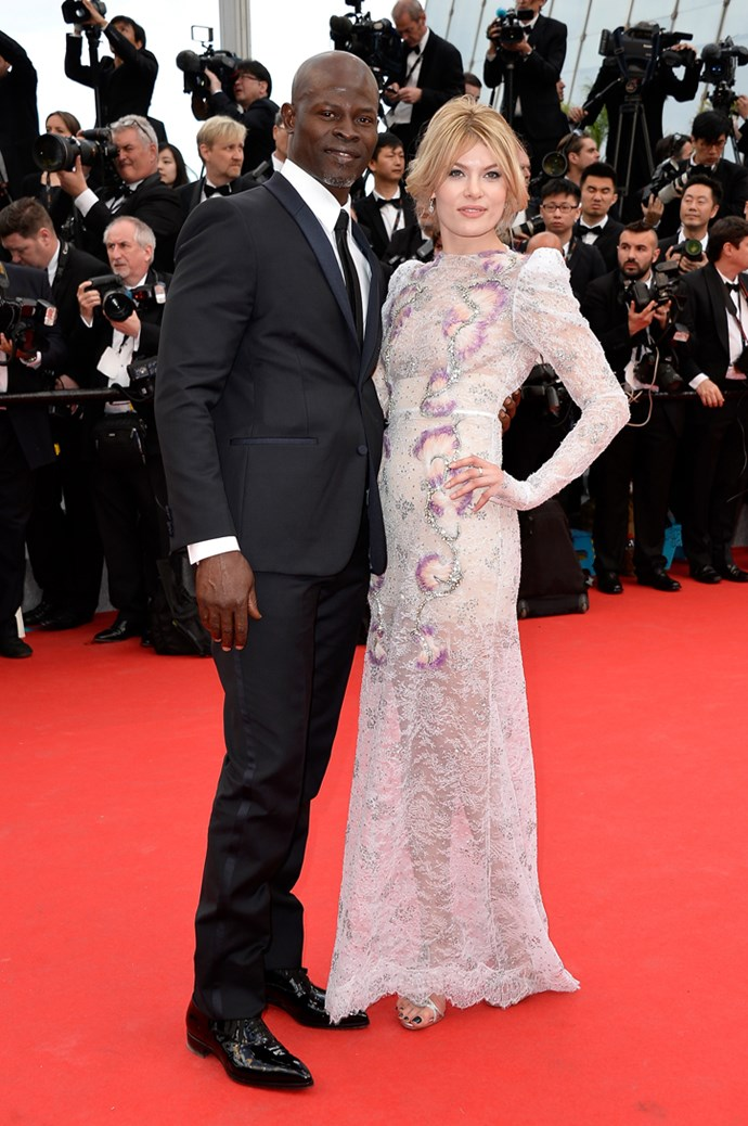 <em>How to Train Your Dragon 2</em> actor Djimon Hounsou and unknown guest wearing a lilac lace dress at the 67th Annual Cannes Film Festival.