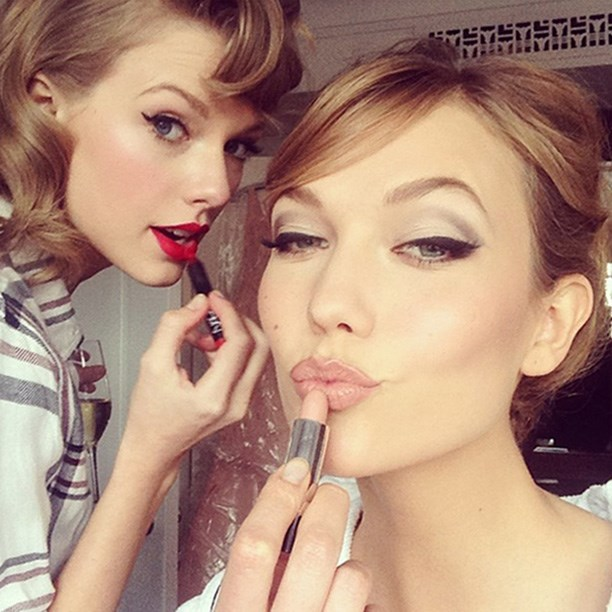 Taylor Swift paints on a red lip while getting ready with model pal, Karlie Kloss for the 2014 Met Gala.