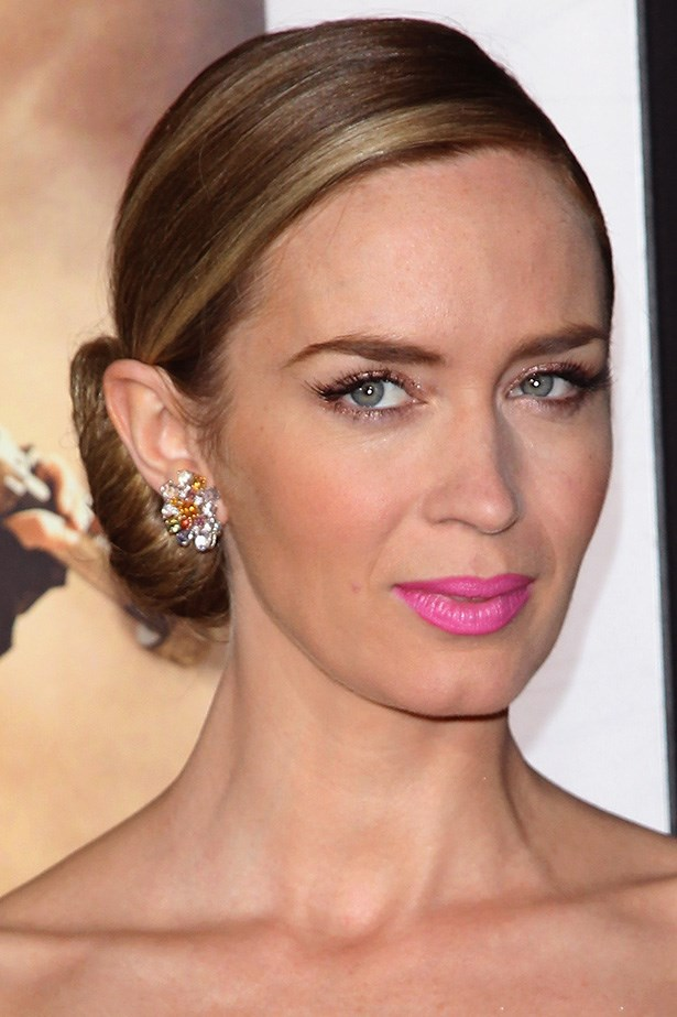 British actress, Emily Blunt contrasts a sophisticated side bun with a bright barbie lip at the New York premiere of <em>Edge of Tomorrow</em>.