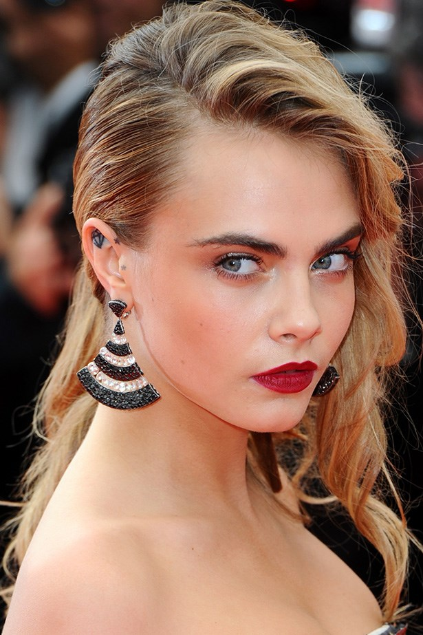 Cara Delevingne shows off her rock chic earrings with the help of her deep parted 'do at <em>The Search</em> premiere at Cannes.