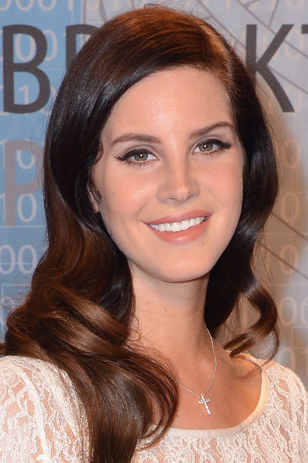 Del Rey shows off sleek side-parted curls and luminous skin at an event in California.