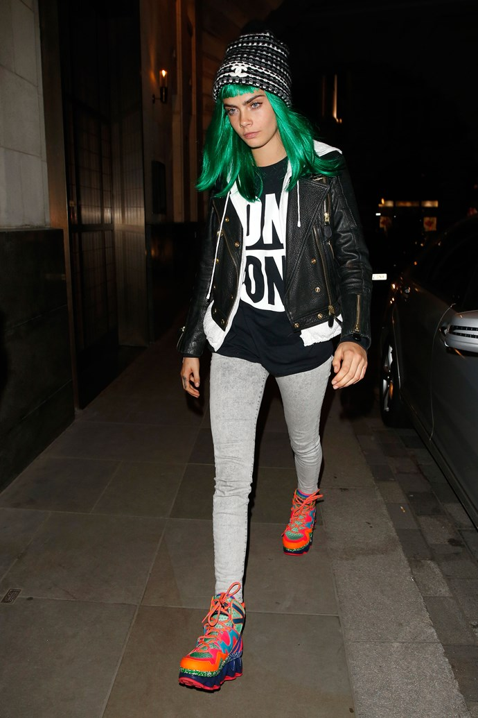 Cara Delevingne embraces the sporty-chic trend in neon sneakers and a designer beanie. Bam!