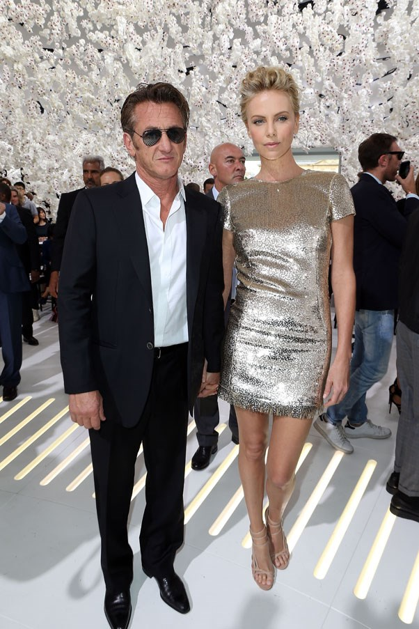 Charlize Theron showed off her glamazonian pins at the Dior show in this golden mini dress, her accessory? A slick-looking Sean Penn.