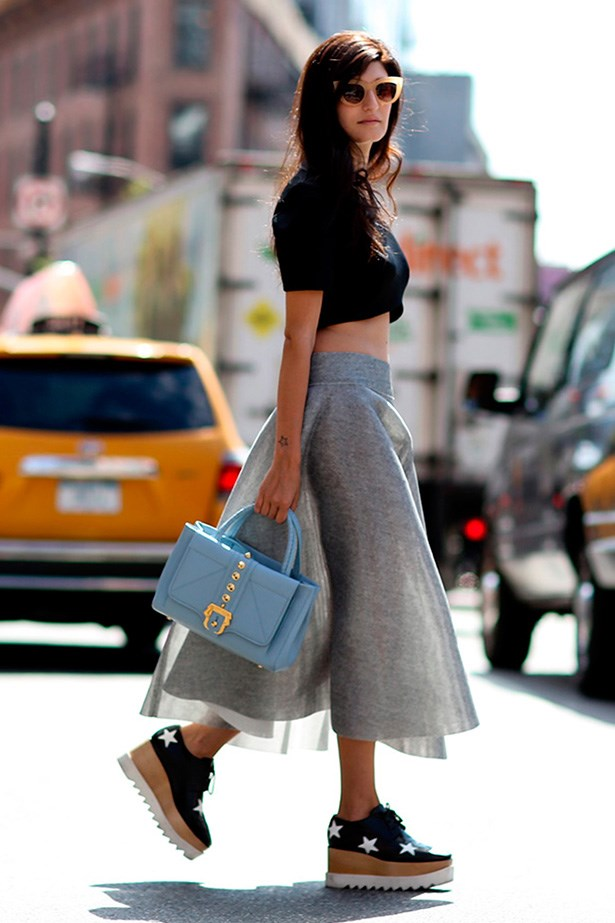 This fashion week star rocks a midriff top with a full-skirt and mega-platforms.