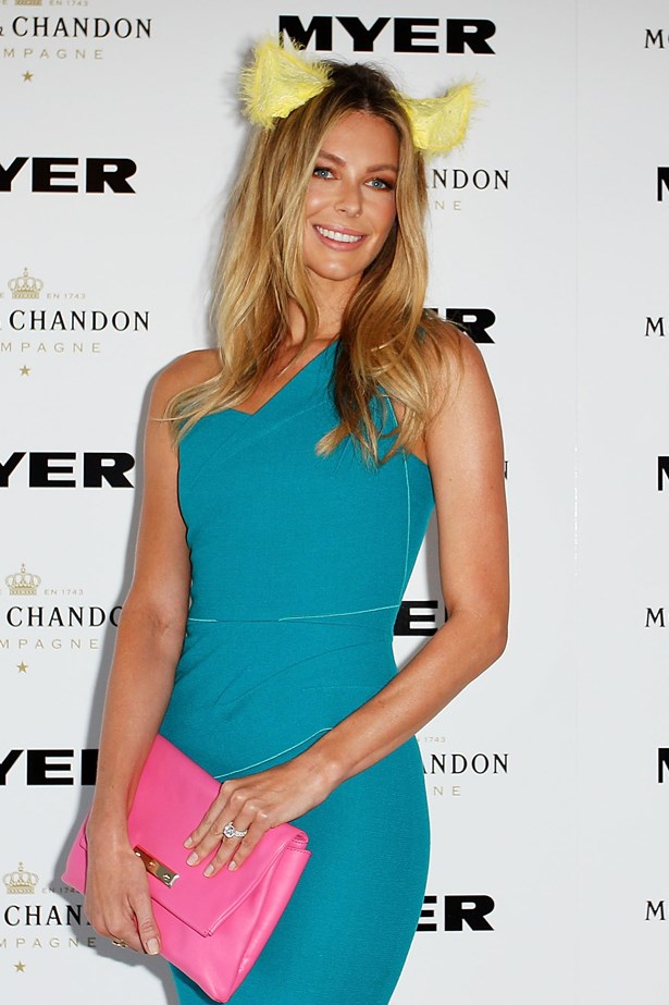 Jennifer Hawkins at Randwick Racecourse wearing a teal dress offset with a pink clutch and a fun animal ear headpiece.