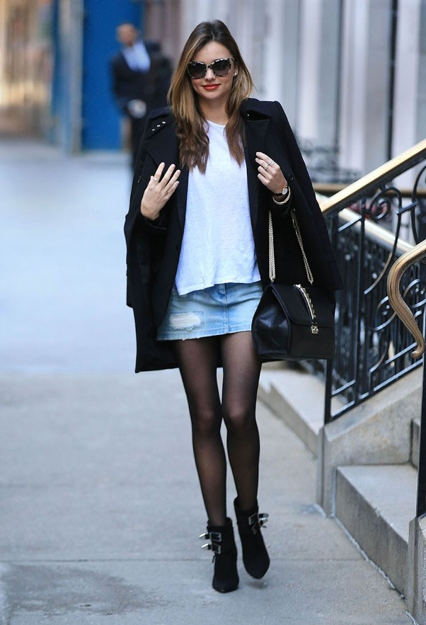 Looking stylish in a denim skirt and cape in November 2013.