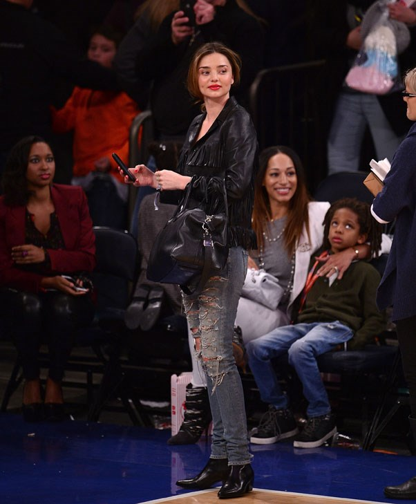 Casual chic in ripped jeans, Saint Laurent Boots and a fringed leather jacket while courtside at the New York Knicks game on December 27, 2014.