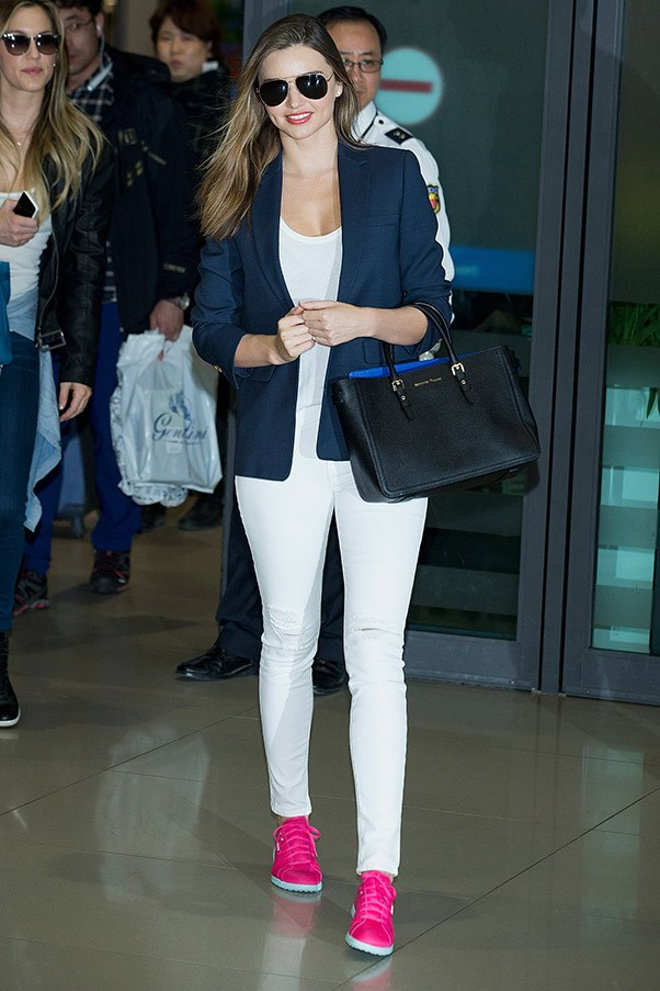 At the airport arriving in South Korea on 31 March, breaking up an all-white ensemble with dark accessories and colour-pop pink sneakers.