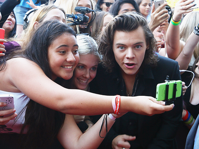 Harry Styles gets pinched by a fan on the ARIAs red carpet