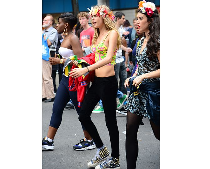 The supermodel flaunts her youth in her finest festival get up: floral wreath, bright crop, leggings and connies!