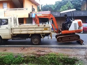 Loading an excavator onto a truck without ramps.